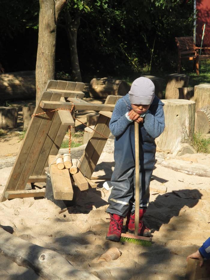 Ein Kind steht im Sandkasten und ruht sich aus.